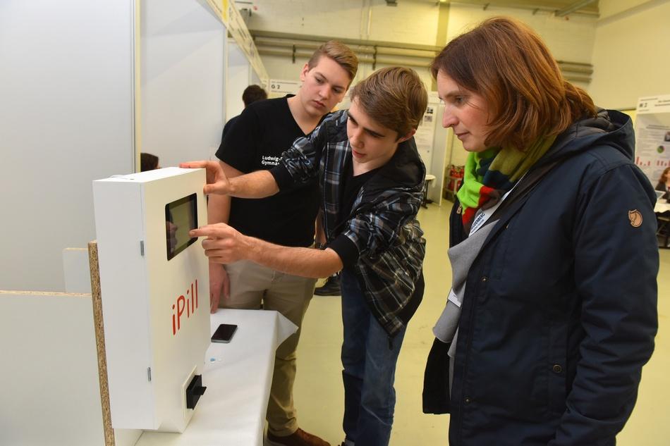 Timo Merke (Mitte) erklärt einer Besucherin, wie der intelligente Tablettenspender funktioniert.  Foto: Peter Dorn